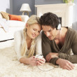 Couple Listening To MP3 Player On Headphones Relaxing Laying On — Stock Photo
