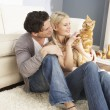 Couple Taking Playing With Pet Cat At Home - Stock Photo