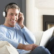 Man Using Laptop Wearing Headphones Relaxing Sitting On Sofa At - Stock Photo