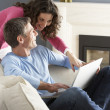 Couple Using Laptop Relaxing Sitting On Sofa At Home — Stock Photo