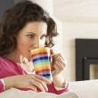 Woman Relaxing On Sofa At Home Drinking Cup Of Coffee — Stock Photo