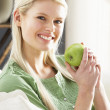 Woman Relaxing On Sofa Eating Apple At Home — Stok fotoğraf