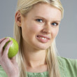 Woman Relaxing On Sofa Eating Apple At Home — Foto Stock