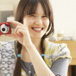 Young Woman Taking Photograph On Digital Camera At Home - Foto Stock