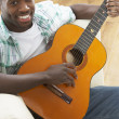 Young Man Relaxing Sitting On Sofa Playing Acoustic Guitar — Stock Photo