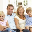 Family sitting in living room smiling - Stockfoto