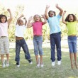 Five young friends jumping — Stock Photo #4838826