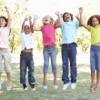 Five young friends jumping — Stock Photo