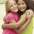 Stock Photo: Two Girls In Park Giving Each