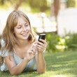 teenage girl verlegung in park mit handy — Stockfoto #4838891