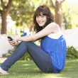 Portrait Of  Teenage Girl Sitting In Park Using Mobile Phone - Stock Photo