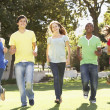 Group Of Teenagers Running Through Park — Stock Photo