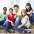 Group Of Teenage Friends Sitting On College Steps Outside - Stock Photo