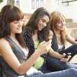 Stock Photo: Group Of Teenage Students Sitting Outside On College Steps Using
