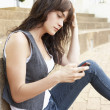 Stock Photo: Unhappy Female Teenage Student Sitting Outside On College Steps