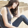 Unhappy Female Teenage Student Sitting Outside On College Steps - Foto de Stock