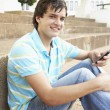 Male Teenage Student Sitting Outside On College Steps Using Mobi — Stock Photo #4838998