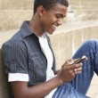 Male Teenage Student Sitting Outside On College Steps Using Mobi - Stock Photo