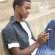 Unhappy Male Teenage Student Sitting Outside On College Steps Us - Stock Photo