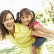 Mother Giving Daughter Ride On Back In Park — Stock Photo