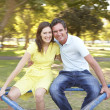 Stock Photo: Young Couple Riding On Roundabout In Park