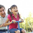 Father And Daughter Riding On See Saw In Playground — Stock Photo #4839141