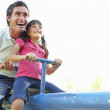 Father And Daughter Riding On See Saw In Playground — Stock Photo #4839142