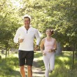 Stock Photo: Middle Aged Couple Jogging In Park