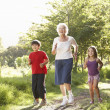Stock Photo: Grandmother Jogging In Park With Grandchildren
