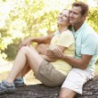 Young Couple In Walking Clothes Resting On Tree In Park - Foto Stock