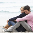 Young Couple On Holiday Sitting On Winter Beach — Stock Photo