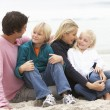 Young Family Sitting On Winter Beach — Stock Photo