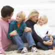 Young Family Sitting On Winter Beach — Stock Photo #4839466