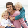 Father And Children Sitting On Winter Beach Together — Stock Photo