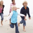 Young Family Running Along Winter Beach — Stockfoto