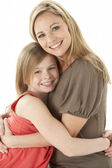 Studio Portrait Of Mother Hugging Young Daughter — Stock Photo