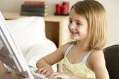 Jeune fille à l'aide d'ordinateur à la maison — Photo