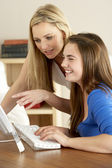 Mother And Teenage Daughter At Home Using Computer — Stock Photo