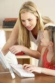 Madre e hija en casa usando la computadora — Foto de Stock