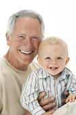 Studio Portrait Of Grandfather Holding Grandson — Stock Photo