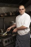 Mužský šéfkuchař připravuje jídlo na sporáku v kuchyni restaurace — Stock fotografie