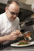 Chef Adding Sauce To Dish In Restaurant Kitchen — Stockfoto