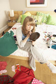 Teenage Girl Putting On Make Up In Untidy Bedroom — Stock Photo