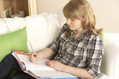 Teenage Girl Studying At Home Sitting On Sofa — Stock Photo