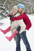 Man Giving Woman Piggyback In Snowy Woodland — Stock Photo