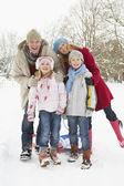Family Pulling Sledge Through Snowy Landscape — Stock Photo