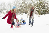 Family Pulling Sledge Through Snowy Landscape — Stock Photo