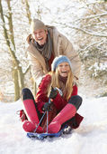 Couple Sledging Through Snowy Woodland — Stock Photo