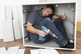 Man Trapped Whilst Assembling Flat Pack Furniture — Stock Photo