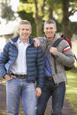 Two Male Friends Walking Outdoors In Autumn Park Together — Stock Photo